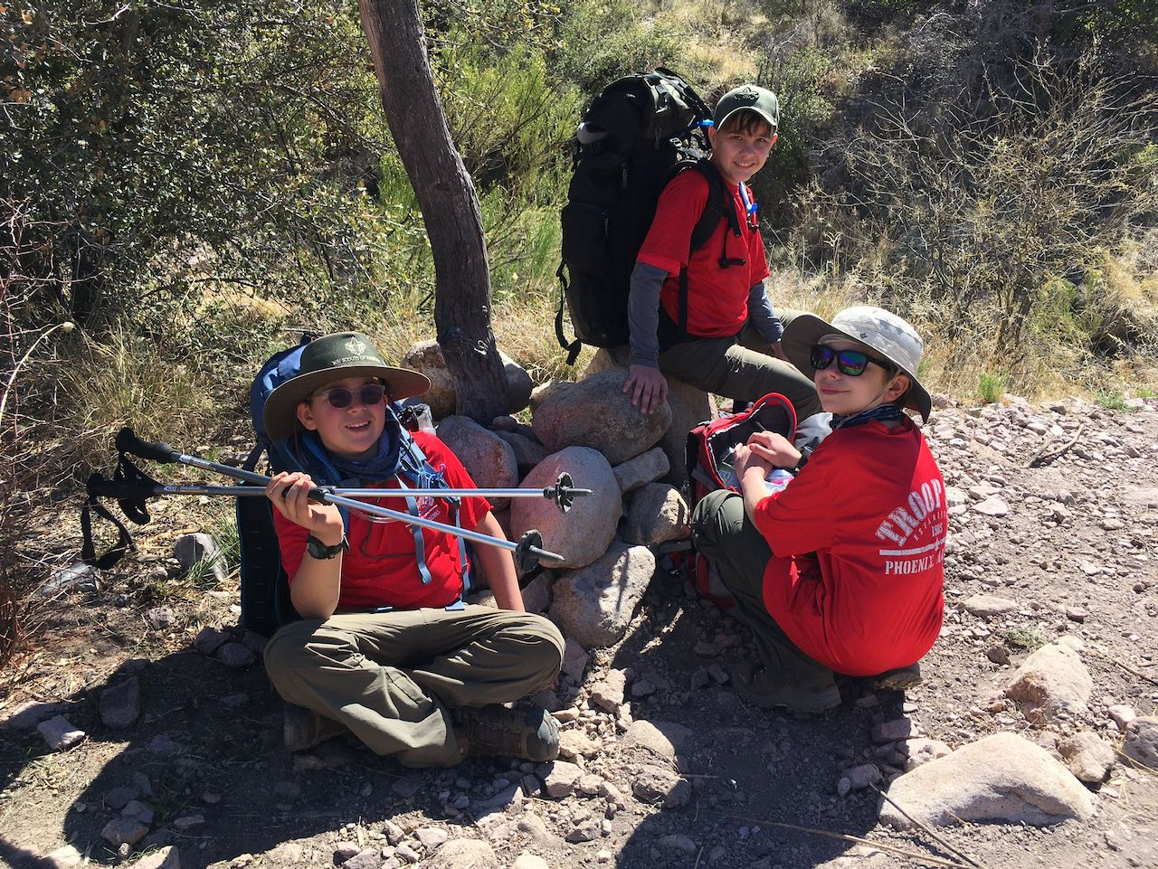 3 scouts sitting on trail